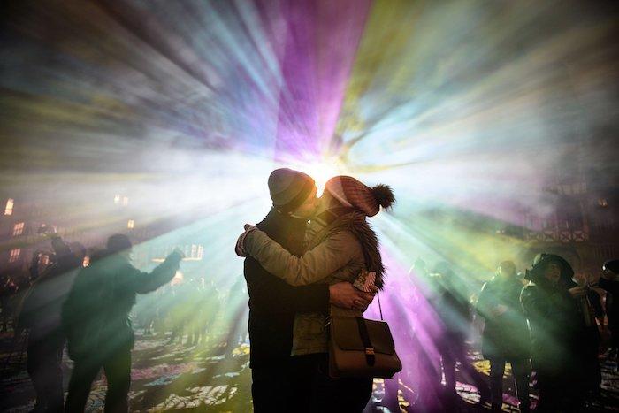 zwei sich küsende menschen, licht mit vielen farben und ein liebespaar, eine junge frau mit tasche und schal und einem hut