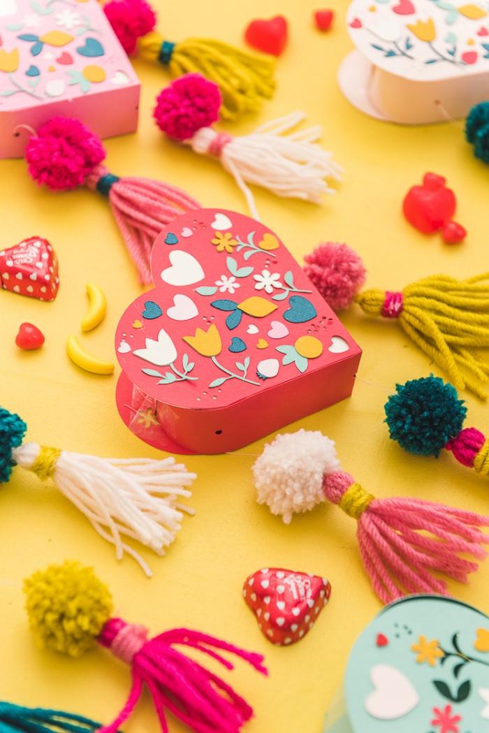 selbstgemachtes muttertagsgeschenk, box in der form von herzen dekoriert mit troddeln und kleinen papierblumen