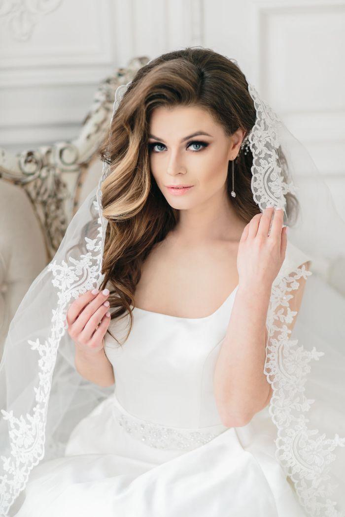 flechtfrisuren hochzeit, eine schöne braut mit langen braunen haaren, wellen in dem haar, weißes kleid, lange ohrringe