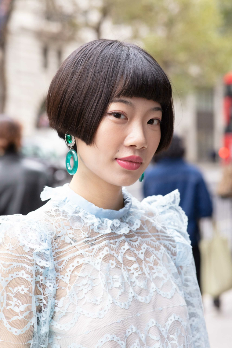 bob frisuren in aisatischem stil, schwarze haare, lange große ohrringe, blaugrün, rosarote lippen, weiße bluse aus spitze
