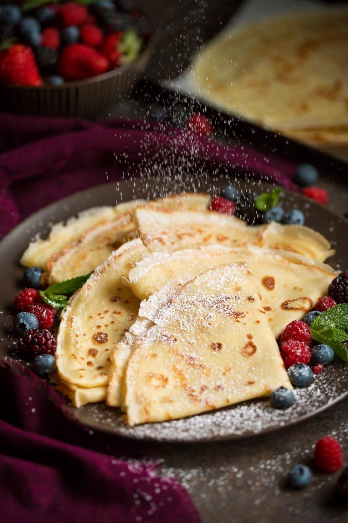 pfannkuchen mit vanille, garniert mit blaubeeren, himbeerne und puderzucker, frühstück brunch