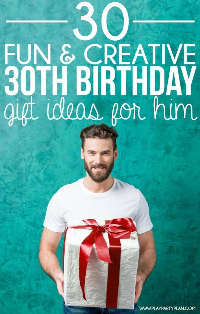 geschenke für den freund, geschenk idee zum 30 geburtstag, ein mann mit weißem shirt hält ein großes paket mit roter schleife