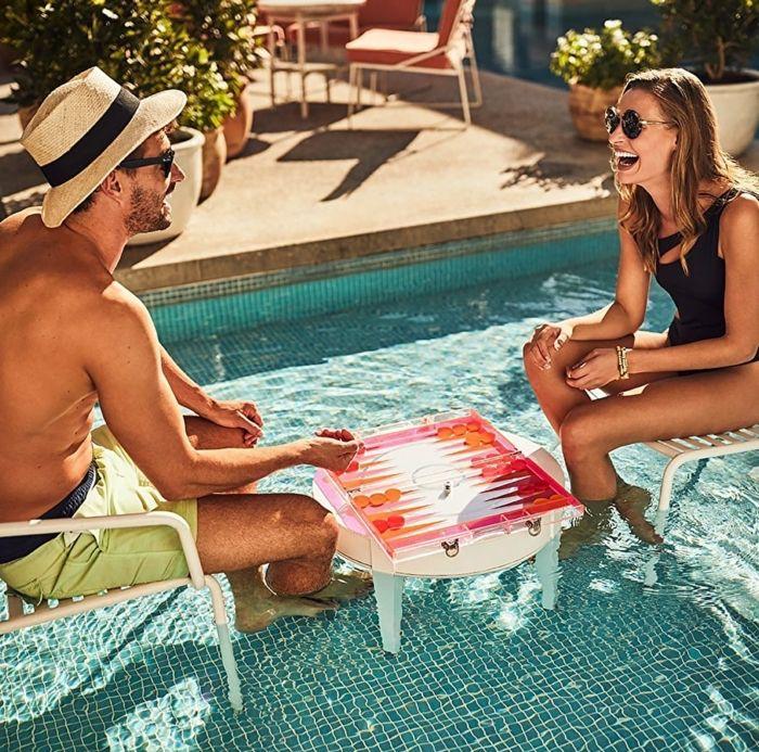 geburtstagsgeschenk für freund, mann und frau sitzen in pool und spielen tablett