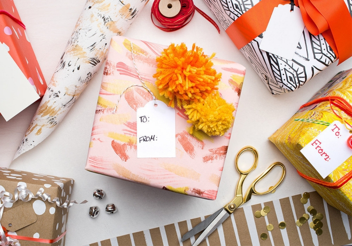 geschenke zum muttertag, die bestne ideen, buntes geschenkpapier, bommeln aus gelbem garn, muttertagsgeschenk verpacken