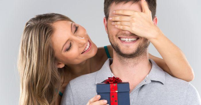 besondere geschenkideen für männer eine frau überrascht ihren freund mit einem geschenk in schöner box blau mit roter schleife