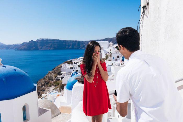 Heiratsantrag in Santorini, Frau mit rotem Kleid und Mann mit weißem Hemd, fantastische Aussicht
