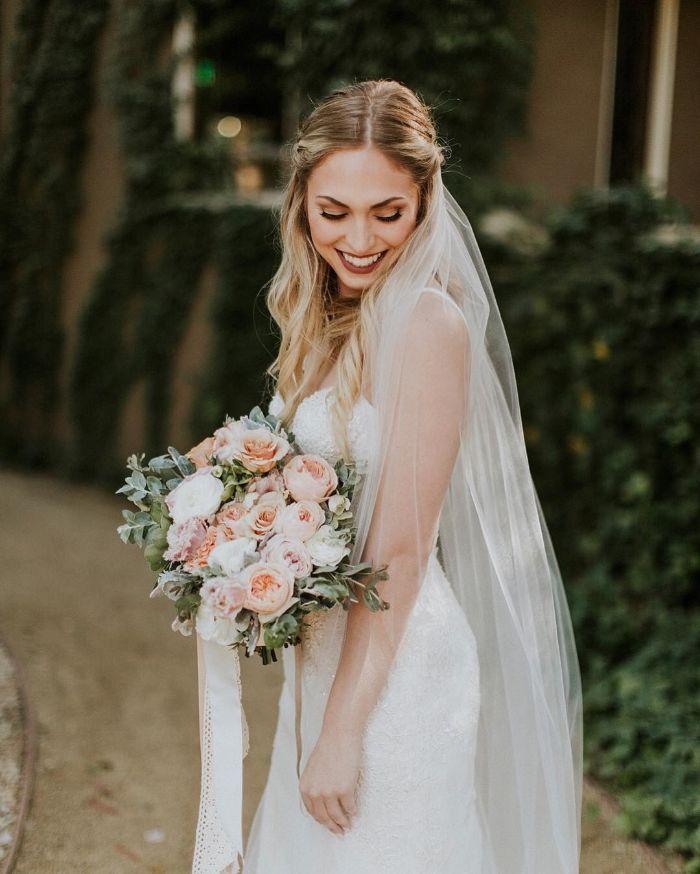 Brautfrisuren mit Schleier, langes blondes haar, blumenstrauß weiß und rosa, seitlich gebundene haare, beachwaves