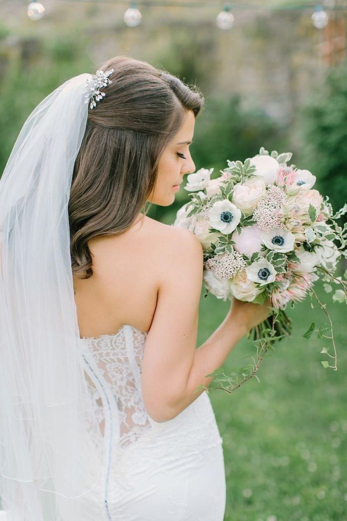 Brautfrisuren mit Schleier, frisur mit haarschmuck und schleier angehängt daran, blumenstrauß