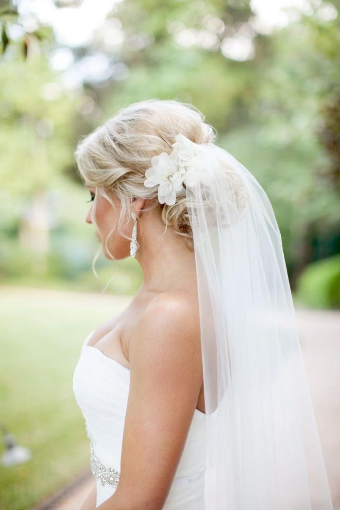 hochzeitsfrisuren halboffen mit niedrig gebundene haare, blonde braut mit schleier, seitliches foto