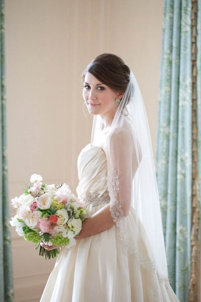 hochzeitsfrisuren halboffen eine schöne und elegante braut mit ihrem kleid, schleier, transparente ärmeln und schöner blumenstrauß