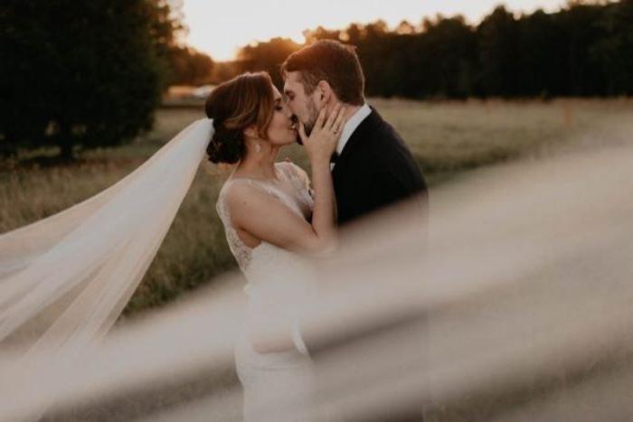 brautfrisur bob mit einem sehr langen schleier, braut küsst den bräutigam