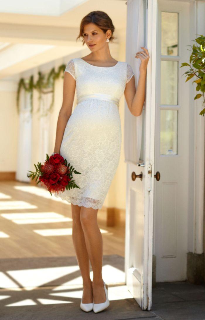 brautkleider für schwangere, eine elegante dame mit kleid aus spitze, roter blumenstrauß