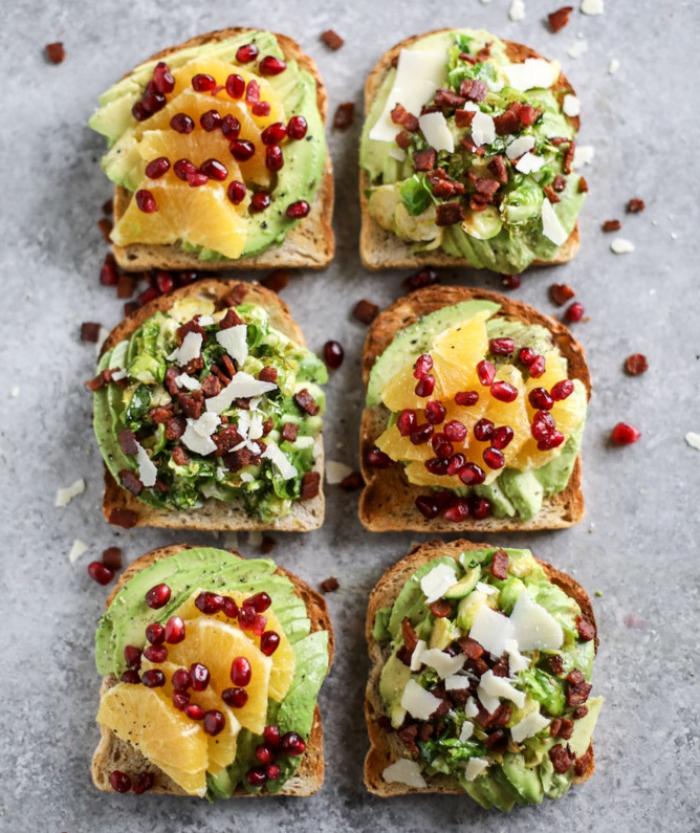 ideen für brunch, brotscheiben mit avocado, orangen und granatapfelsamen, verschiedene zutaten, frühstück