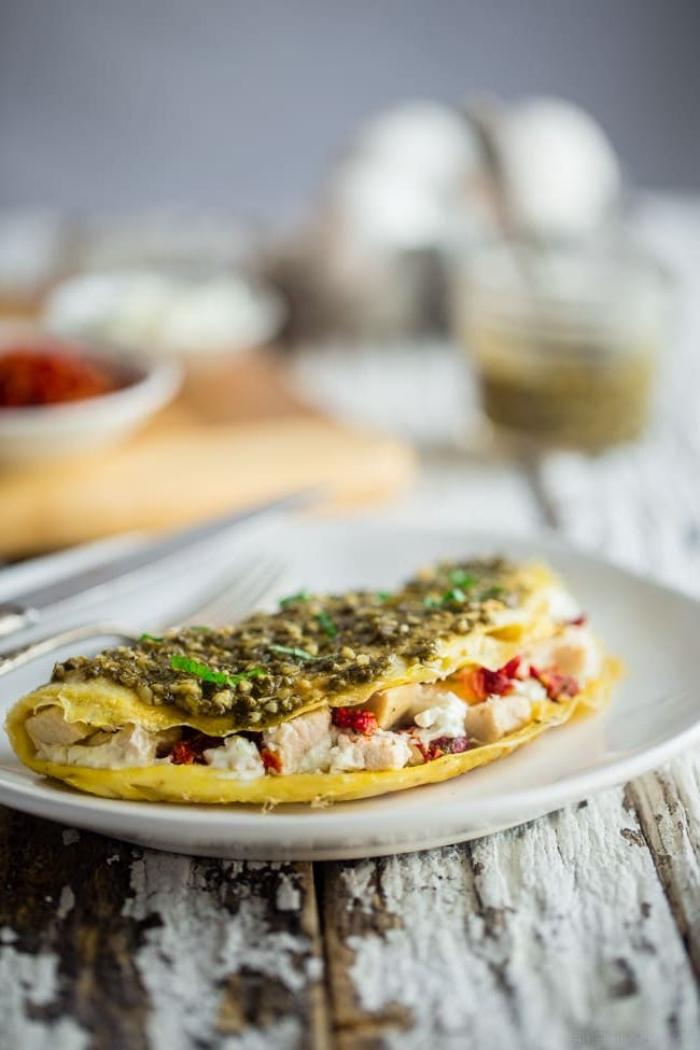 ideen für brunch, omelette mit schinken, paprika, ziegenkäse garniert mit grüßem soße