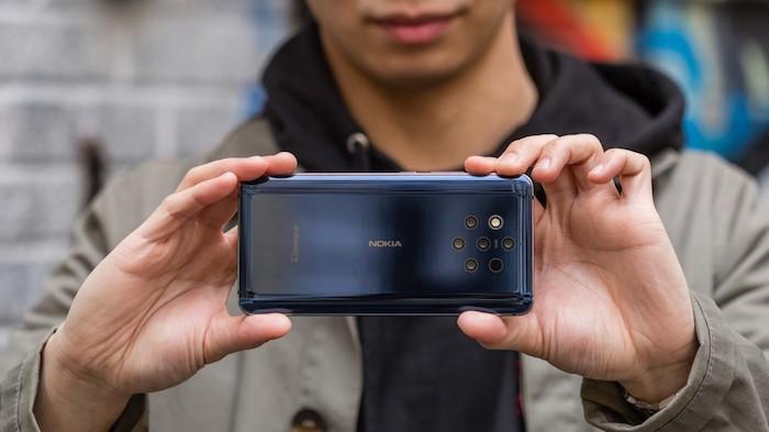 kleines dunkelblaues smartphone nokia 9 pureview mit fünf kleinen zeiss-kameras, ein junger mann, zwei hände