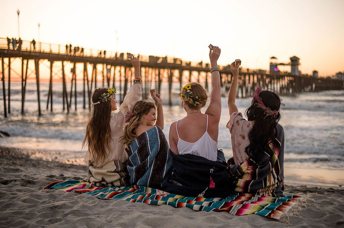 Junggesellinnenabschied auf dem Strand, Sonnenuntergang zusammen mit besten Freundinnen beobachten