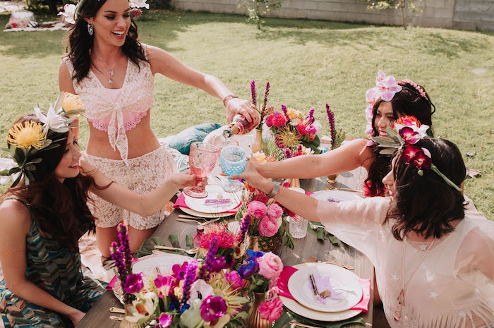 Gartenparty für die Braut organisieren, viele Blumen auf dem Tischen und in den Haaren aller Damen, Champagner genießen