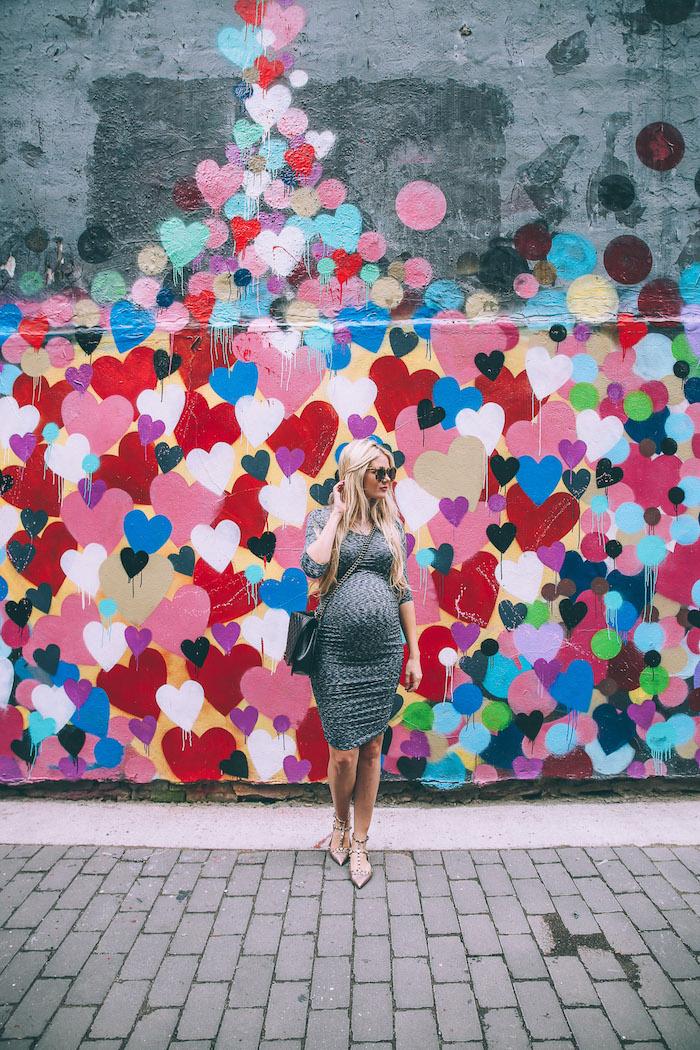 Enges knielanges Umstandskleid in Grau, im Hintergrund viele bunte Herzen an Wand