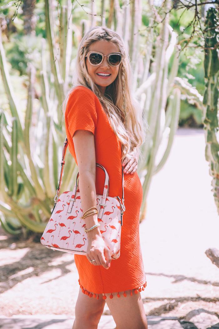 Kurzes Umstandskleid in Orange mit kurzen Ärmeln, weiße Handtasche mit Flamingo Print