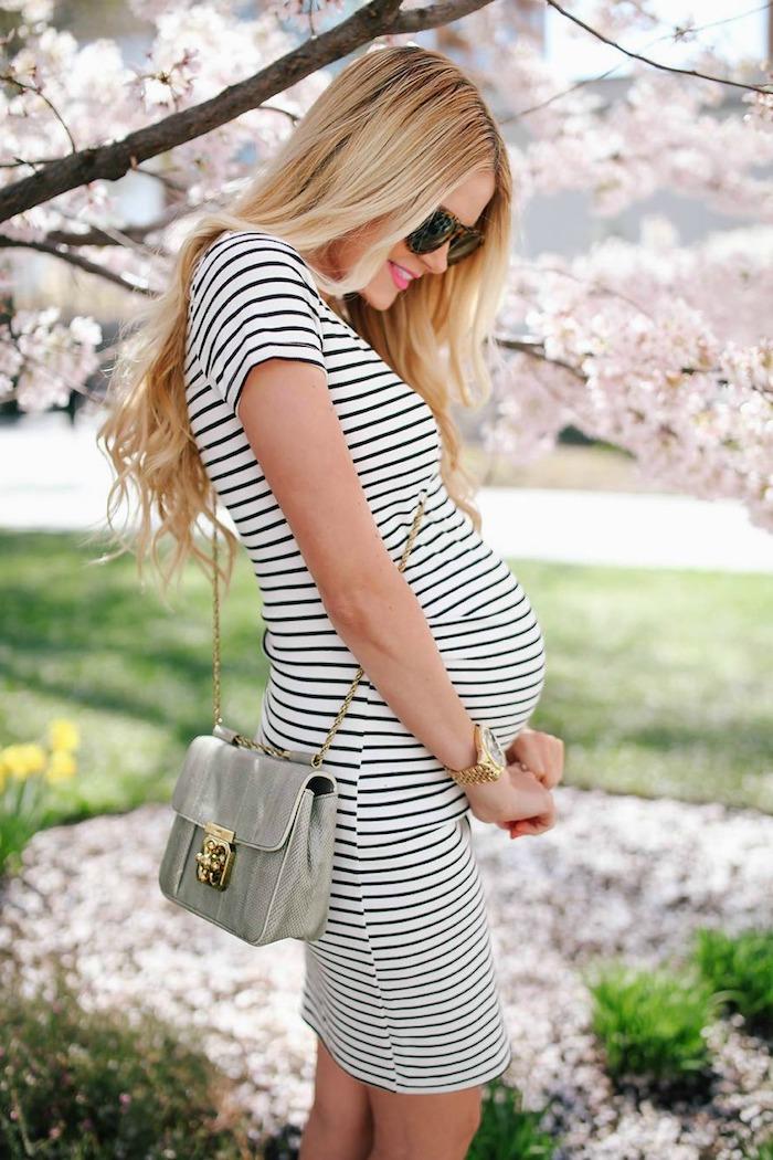 Gestreiftes knielanges Kleid in Schwarz und Weiß für Schwangere, lange blonde Haare, Frühlingsbaum im Hintergrund