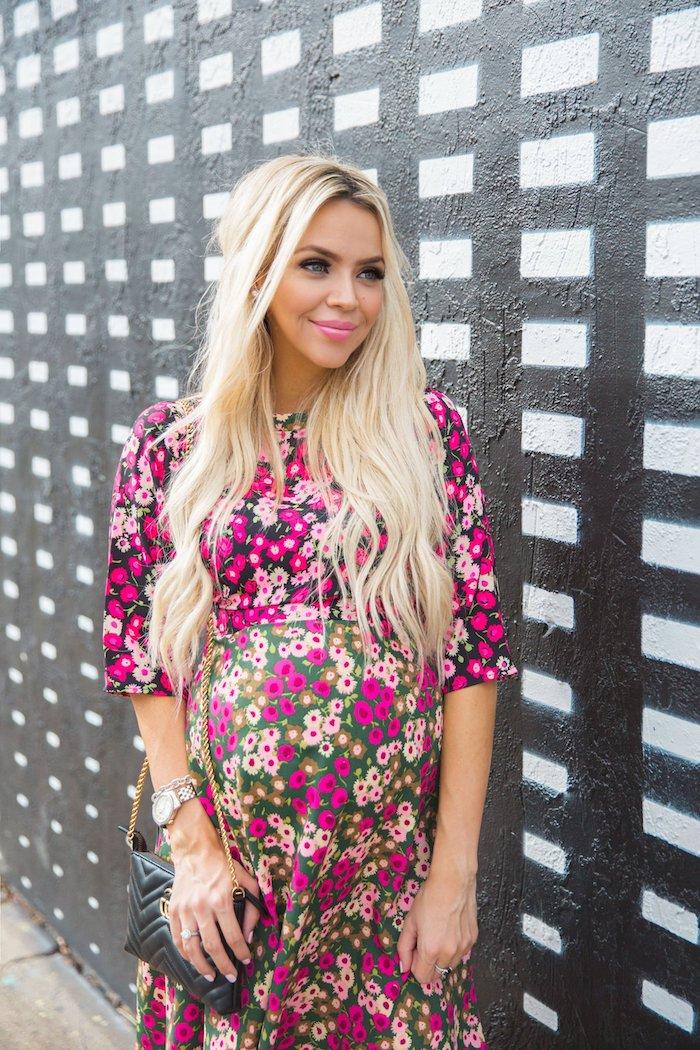 Sommerkleid für Schwangere in fröhlichen Farben mit Blumenmuster, halboffene Haare, schwarzer Clutch