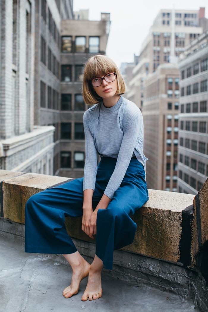 frisuren kinnlang, eine junge frau mit blonden haaren und geraden linien schnitt, blaues outfit