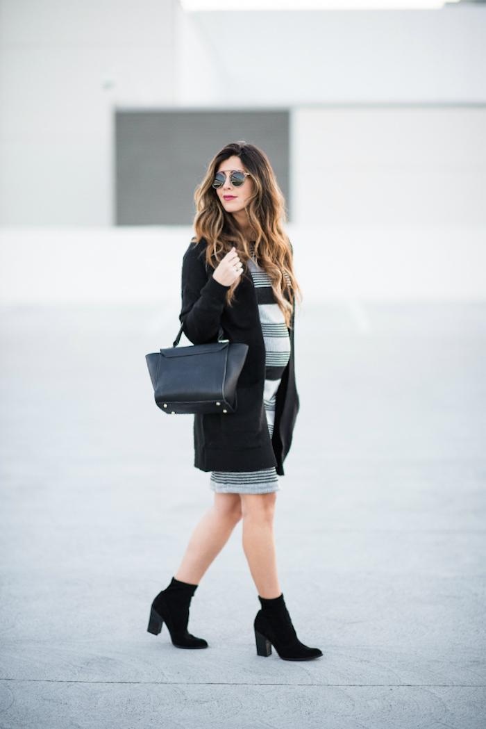 Gestreiftes knielanges Kleid für Schwangere, schwarzer Mantel, schwarze Handtasche und schwarze Stiefel