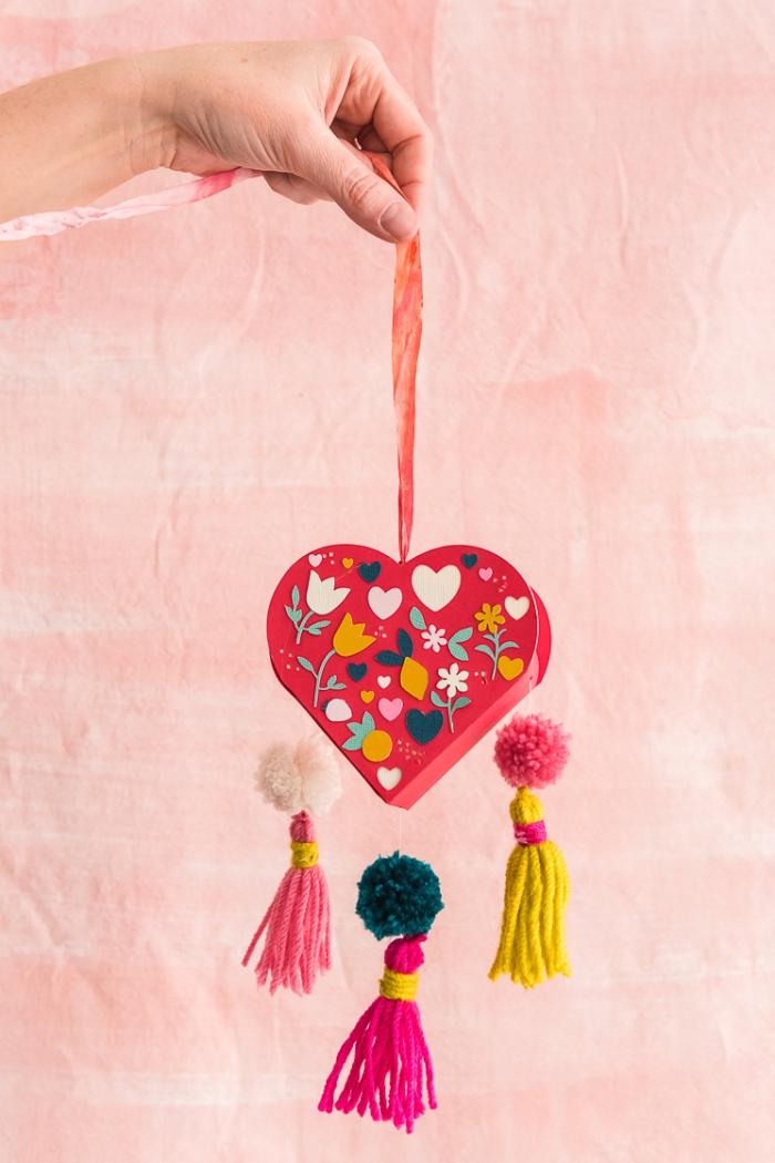 muttertagsgeschenk diy, geschenke selber machen, geschenkbox herz aus rosa papier dekoriert mit troddeln aus garn