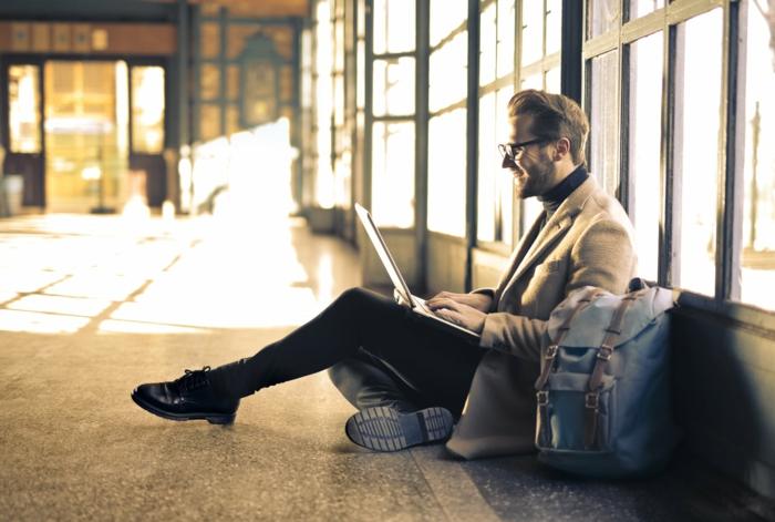 ein Mann mit Brillen sitzt am Laptop in einer Halle, Online-Kunstgalerie Kunstwerke erwerben