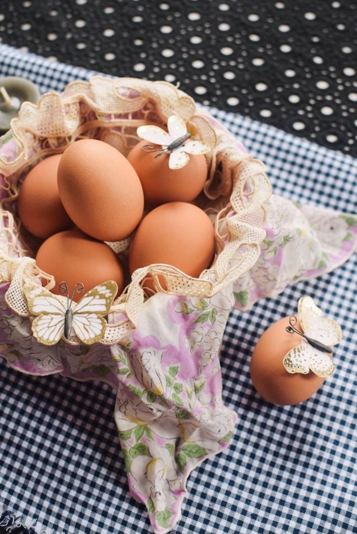 Eier in Osterkörbchen, Tuch mit Blumenmuster und Spitzenelementen, weiße Schmetterlinge aus Papier