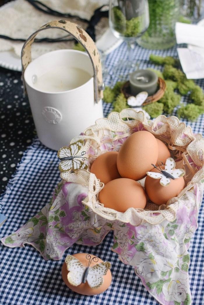 Eier in Osterkörbchen, weiße Schmetterlinge aus Papier, Kerzenhalter mit Deko Moos