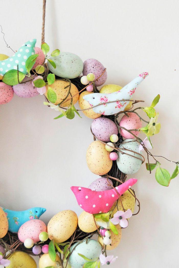 Osterkranz selber machen aus Weidenzweigen, bunte Ostereier und Vögelchen aus Stoff daran befestigen