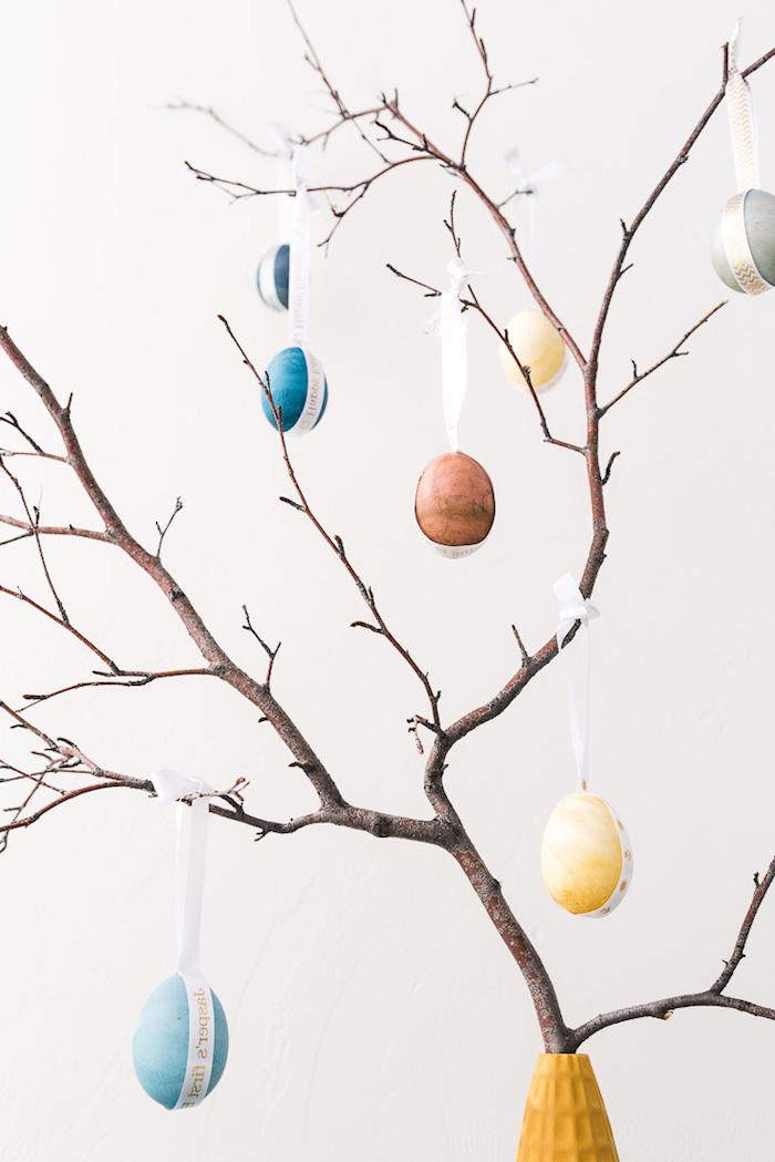 Mini Osterbaum schmücken zu Hause, Zweige in Vase, bunte Ostereier mit weißem Dekoband