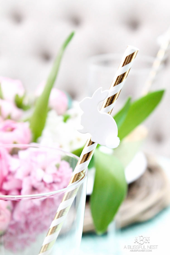 Tischdeko für Ostern, kleiner weißer Osterhase an Strohhalm, rosa Hyazinthen im Hintergrund