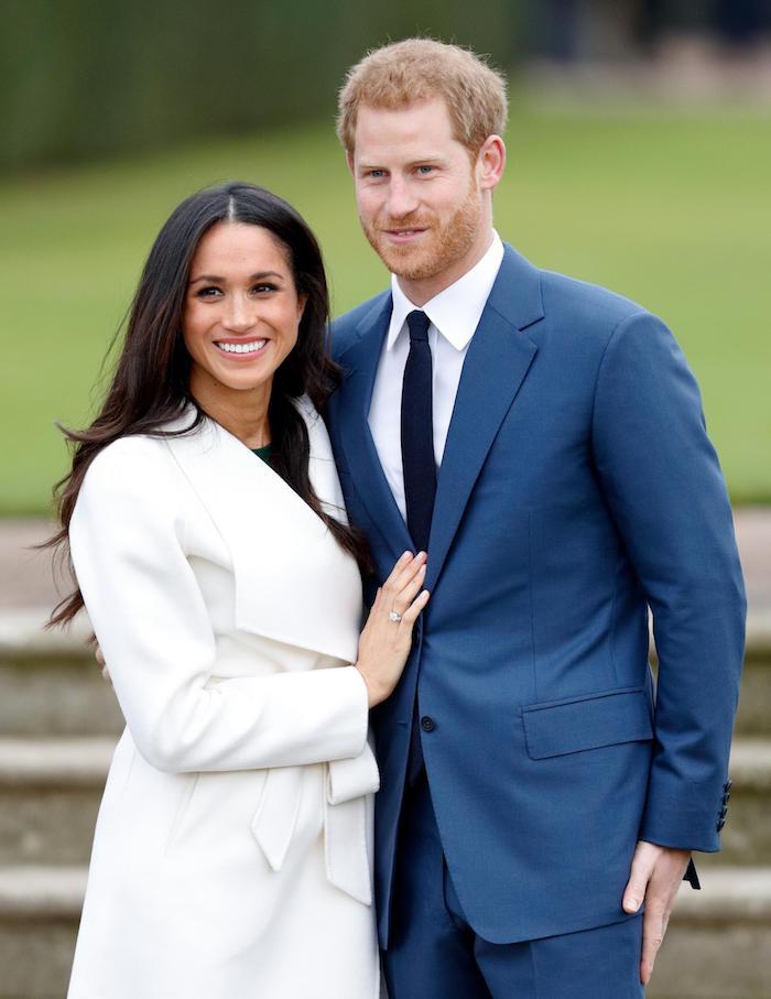 Das glückliche Paar Ehepaar Meghan Markle und Harry, Meghan mit weißem Mantel und offenen gewellten Haaren, Harry im blauem Anzug