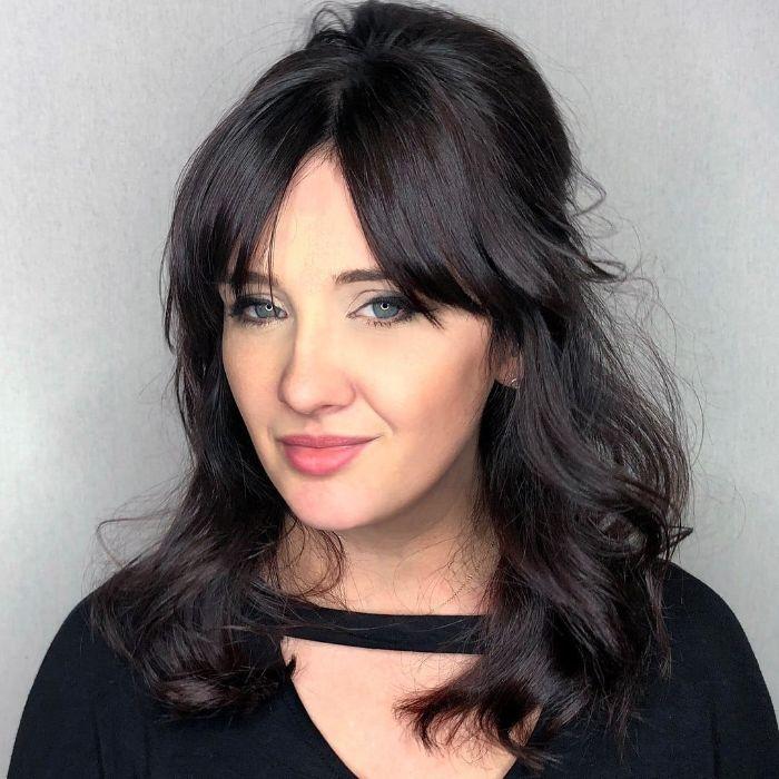 frisuren schulterlanges haar, schwarze haare, pony haare in der mitte getrennt, schwarze bluse, schöne frau