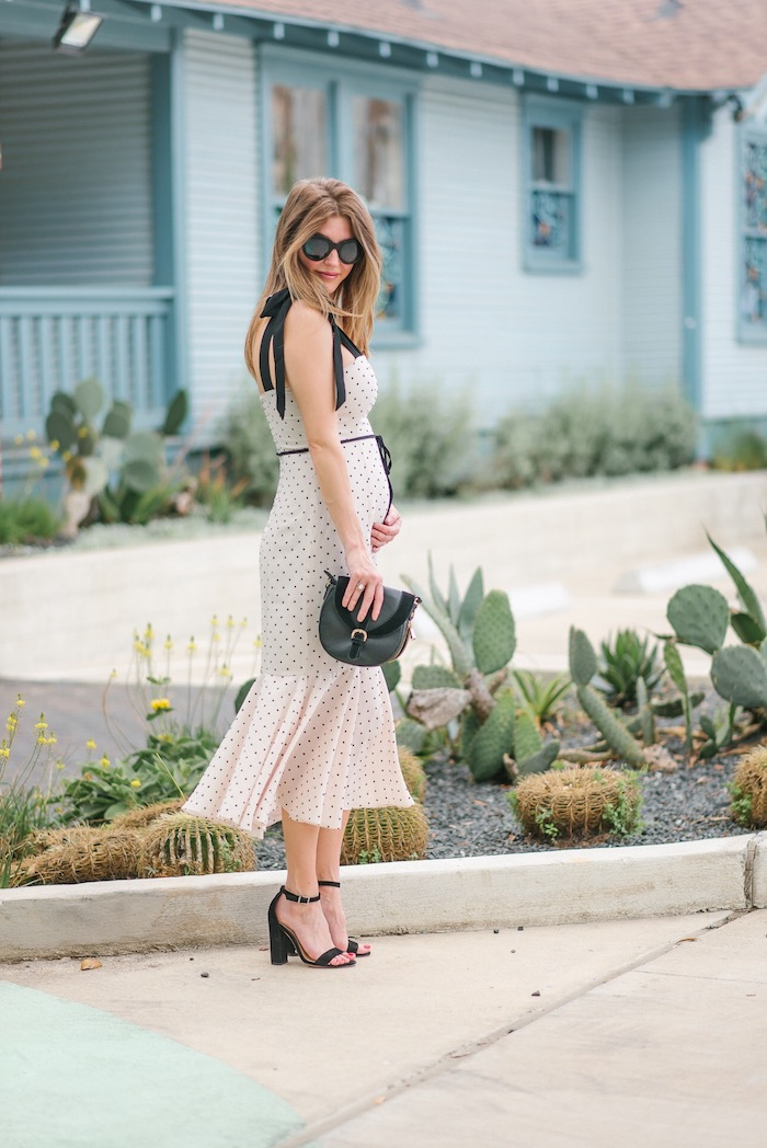 Weißes Sommerkleid mit schwarzen Dots, schwarze Pumps und schwarze Handtasche