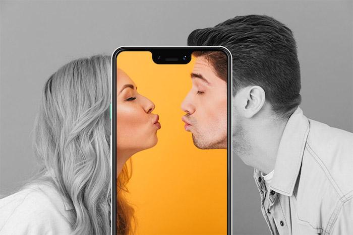 ein liebespaar, zwei sich küssende menschen, junger mann und eine junge frau, ein großes smartphone und eine gelbe wand