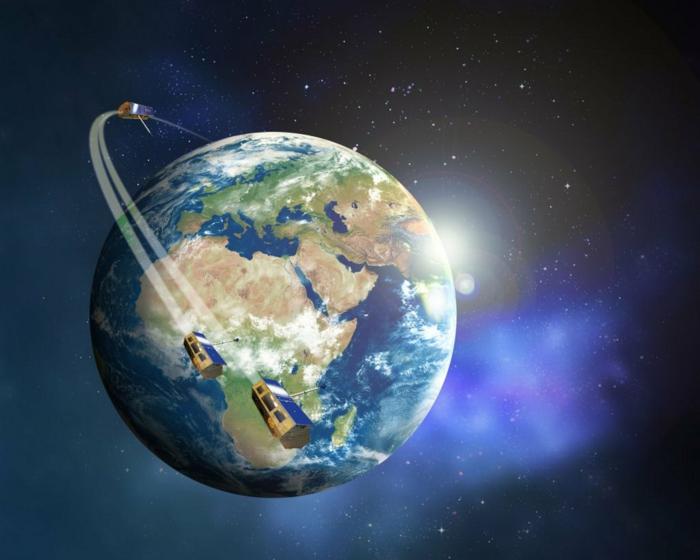 Weltall, drei Satelliten, die das Erde umkreisen, die Sonne zeigt sich hinter der Erde