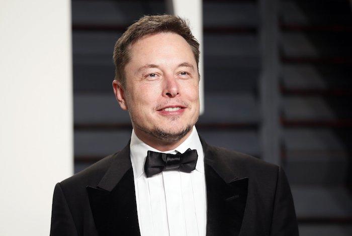 Elon Musk mit elegantem Anzug, schwarzer Sakko, weißes Hemd, schwarze Fliege