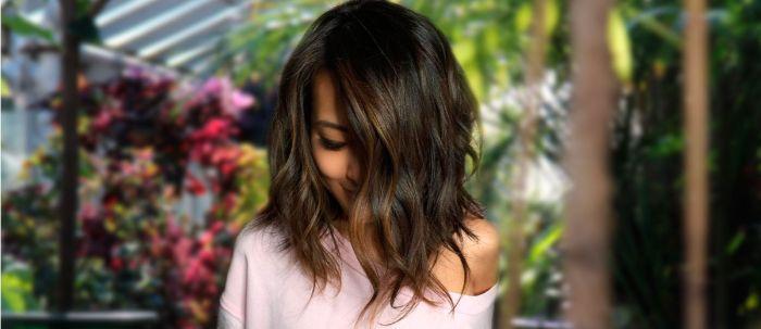 mittellange haare schnitt, eine schöne frau mit dunklen haaren, rosarote bluse, wellen lockiges haar