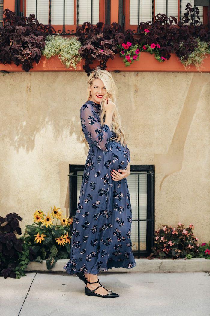 Elegante Umstandsmode, langes dunkelblaues Kleid mit Blumenmuster, schwarze Ballerinas, blonde offene Haare