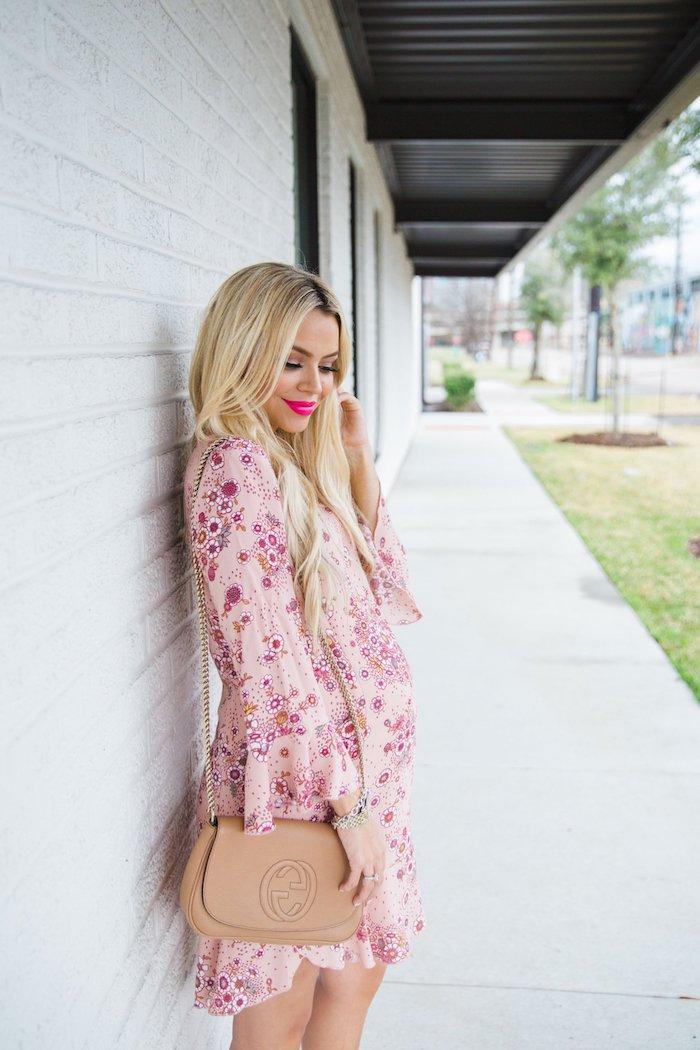 Elegantes Sommerkleid in Zartrosa mit Blumenmuster für Schwangere mit langen Ärmeln, Handtasche in Beige