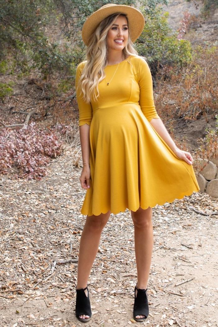 Umstandskleid für besondere Anlässe in Gelb, schwarze Schuhe und Sommerhut, blonde gewellte Haare