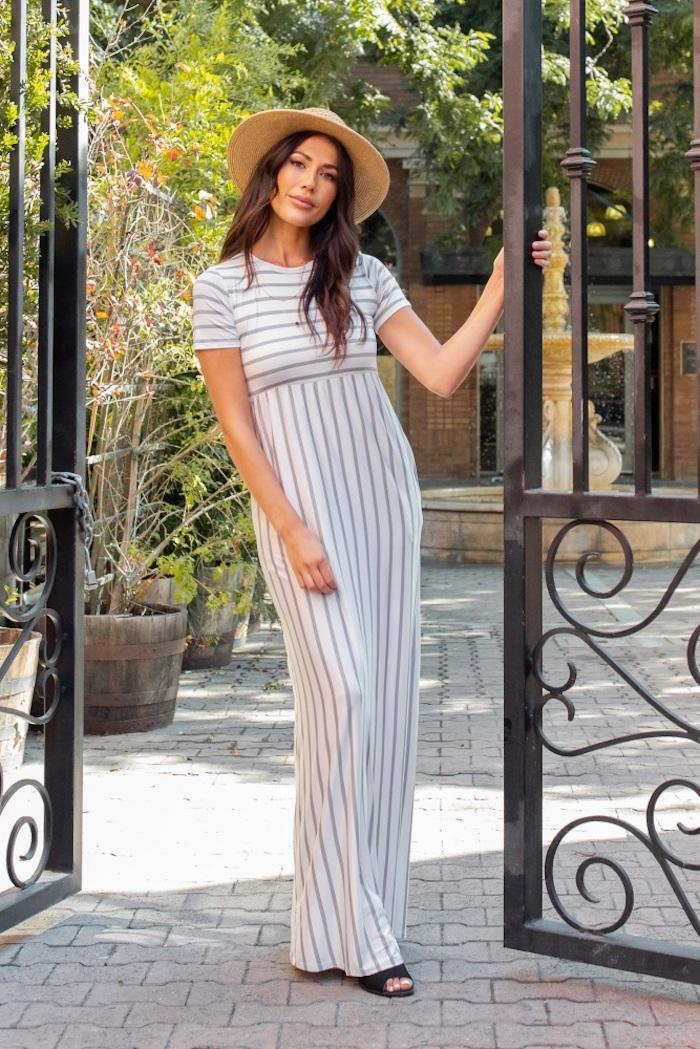 Gestreiftes langes Kleid für Schwangere in Weiß und Grau, schwarze Sandalen und Sommerhut, braune gewellte Haare
