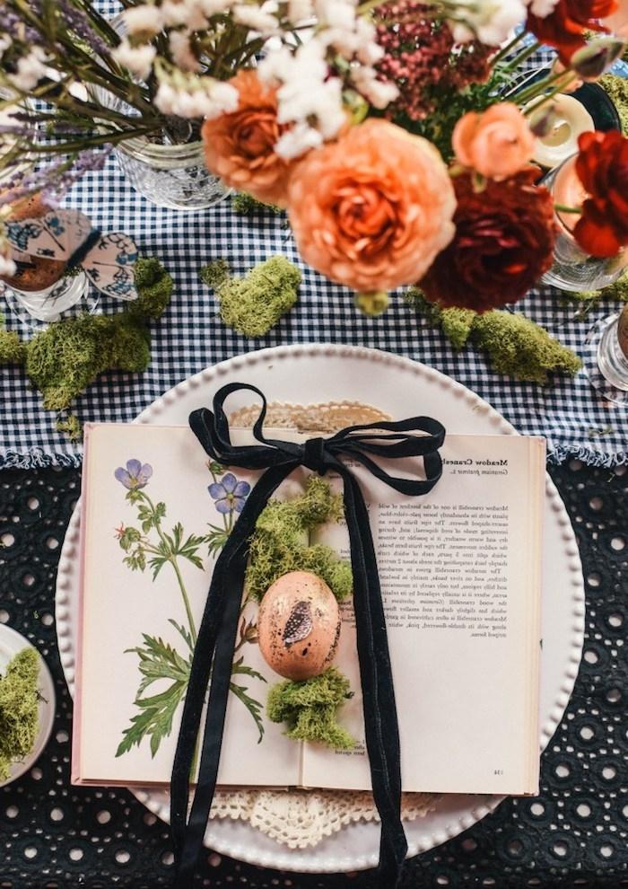 Tischdeko für Ostern, Osterei und Moos auf Buch, schwarzes Dekoband, bunte Blumen in Einmachglas