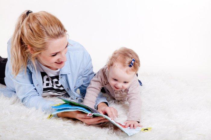 Mama und süßes Baby lesen Buch zusammen, das Lesen feiern am 23. April
