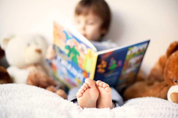 Kleiner Junge liest Kinderbuch, zwei große Teddybären auf dem Bett