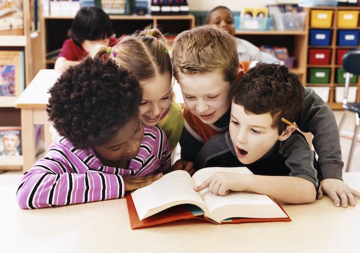 Welttag des Buches feiern am 23. April, Kinder fürs Lesen begeistern, vier Kinder lesen zusammen