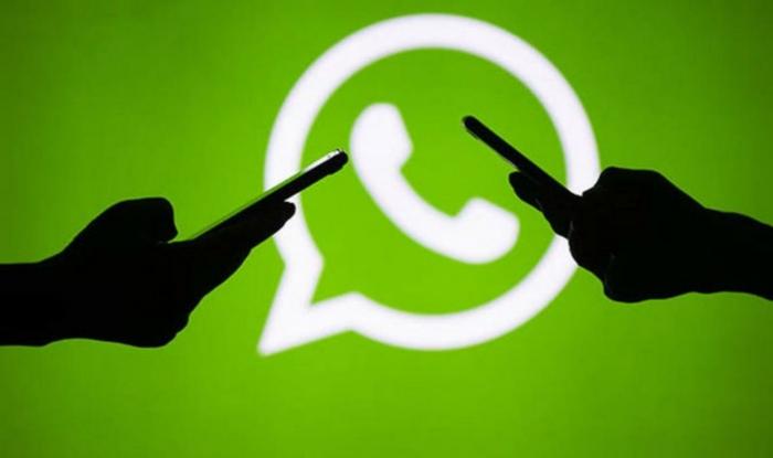 zwei Silhuethen von Händen auf grünen Hintergrund mit WhatsApp Logo